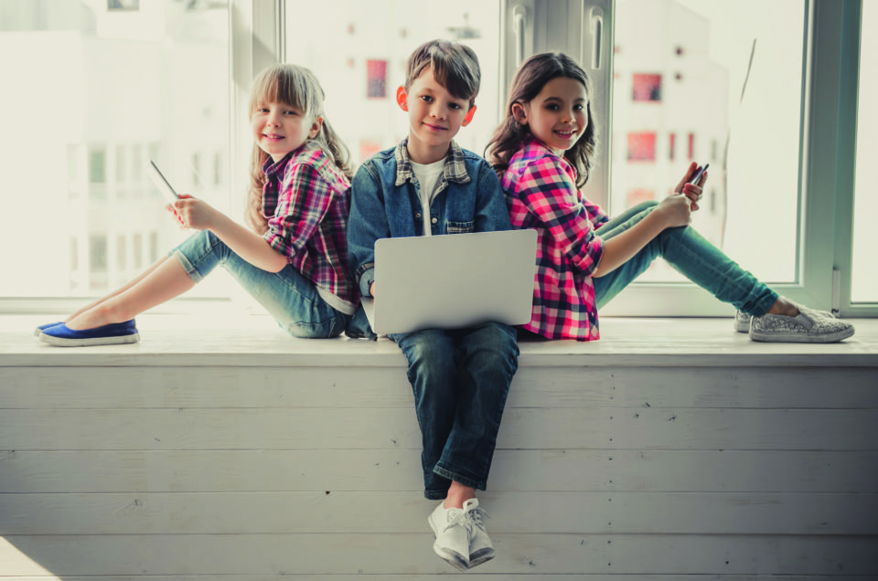 Cheerful kids in casual clothes are using gadgets, looking at camera and smiling while sitting together on the window sill